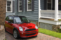red mini cooper in driveway by a blue house